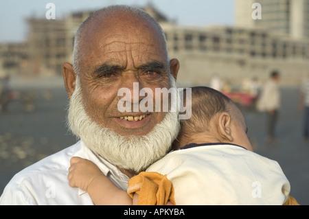 An old Pakistani man holding a baby on Clifton Beach in Karachi, Pakistan. - Stock Photo