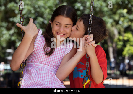 Little boy kissing sister in playground - Stock Photo