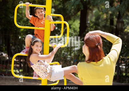Mother and children in playground - Stock Photo