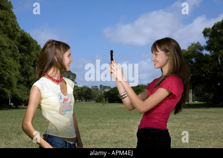Two girls taking pictures with cellular phone - Stock Photo