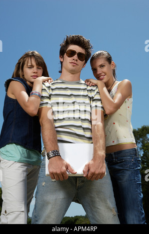 Portrait of three teenagers with notebook - Stock Photo