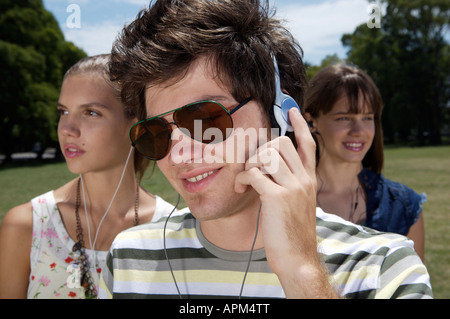 Teenagers listening to music in a park - Stock Photo