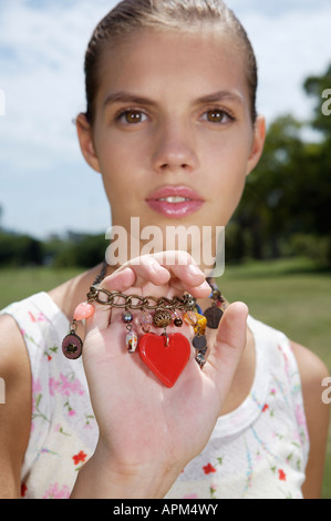 Teenage girl holding a necklace - Stock Photo