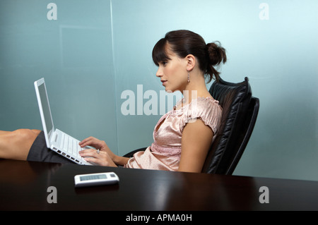 Business woman with her feet on the table using her notebook computer - Stock Photo