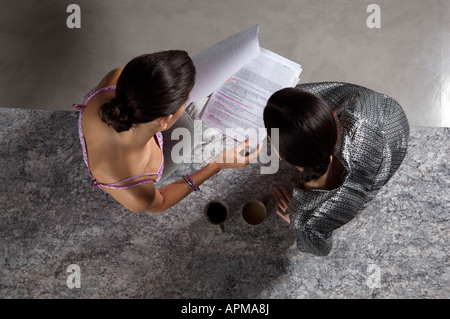 Two business women reading paperwork - Stock Photo