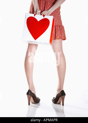Young woman in red dress holding shopping bag behind her back (low section, rear view) - Stock Photo