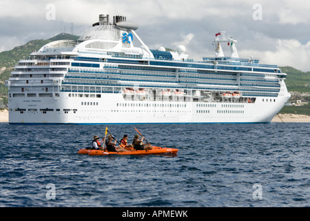 Paddlers in sea kayaks pass cruise ship anchored off Cabo San Lucas Baja California Mexico - Stock Photo