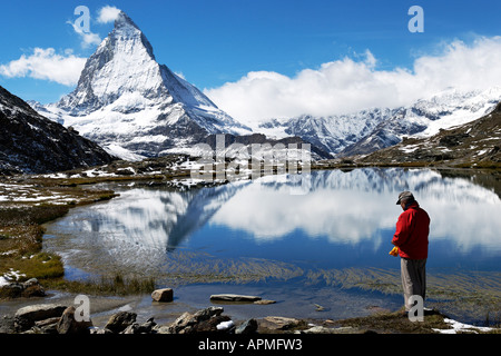 Man reflecting, and Matterhorn reflected in Riffelsee - Stock Photo