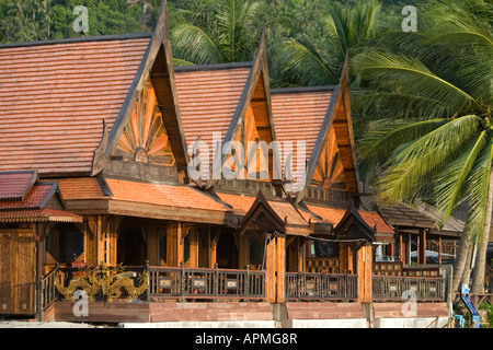 New traditional high pitch roof Thai style hotel rooms on Hat Rin Nok Sunrise Beach Ko Pha Ngan Thailand - Stock Photo