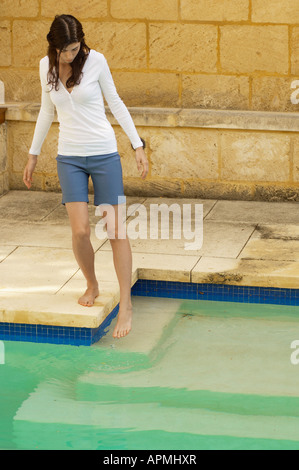 Young woman testing water in swimming pool - Stock Photo