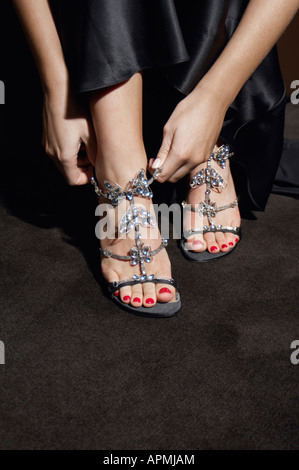 Woman putting high heel shoes on (focus on feet) - Stock Photo