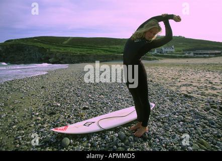 Female surfer stretching on beach, Cornwall - Stock Photo