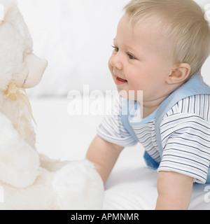 Baby boy (1-2) looking at teddy bear - Stock Photo