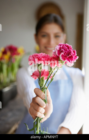 Florist holding Carnation flowers (focus on foreground) - Stock Photo