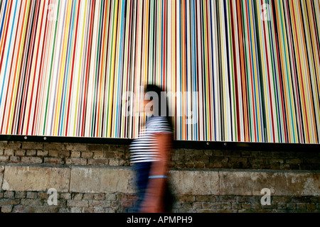 Woman walking past Poured Lines by Ian Davenport on Southwark Street in London - Stock Photo