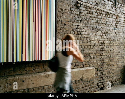 Woman on her mobile phone walking past Poured Lines by Ian Davenport on Southwark Street in London - Stock Photo
