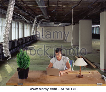Man working alone in messy office - Stock Photo