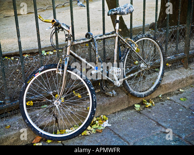 Bicycle chained to a fence for a long time is covered in bird droppings Paris France Europe - Stock Photo