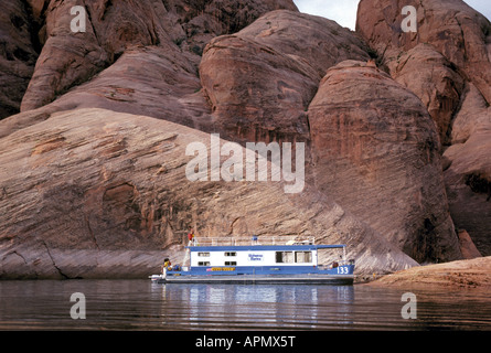 A houseboat moors in a cove surrounded by towering sandstone cliffs on Lake Powell - Stock Photo