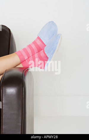 Woman wearing slippers and striped socks - Stock Photo