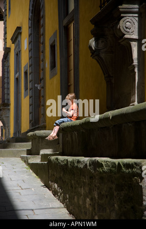 small boy sits quietly alone on a wall in Tuscany - Stock Photo