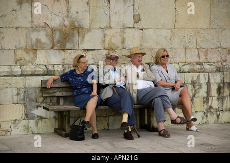 Tourists take a rest outside the Duomo (cathedral) at the top of Barga in Tuscany - Stock Photo