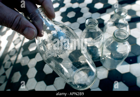 Four empty one pint milk bottles being collected on a traditional doorstep - Stock Photo