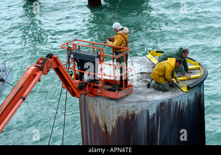 Marine engineers working on large concrete berthing pile in the port of Dunkerque northern France Europe EU - Stock Photo