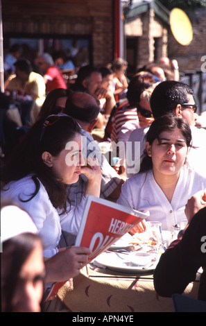 ISTANBUL. Young Turks enjoying Sunday morning coffee and cakes at an outdoor cafe on the Bosphorus in Ortakoy. - Stock Photo