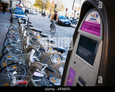 Man cyclist on a hired Velib bicycle rides towards the cycle rack and pay station in Paris, France, Europe - Stock Photo