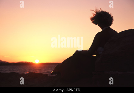 KYRENIA, NORTH CYPRUS. A young woman sitting on the harbour wall in Kyrenia, silhouetted against the setting sun. - Stock Photo