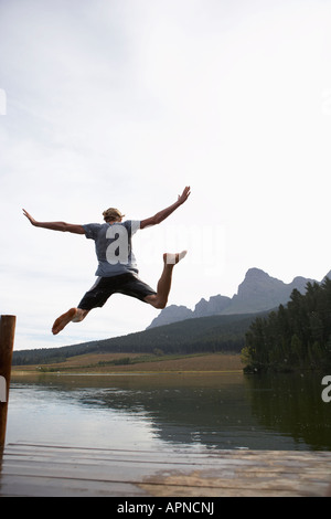 Teenage boy jumping from jetty (rear view), Cape Town, South Africa - Stock Photo