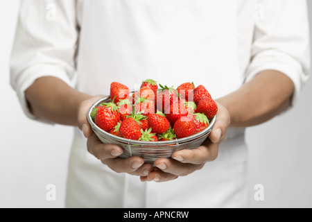 Chef holding bowl of strawberries (mid section) - Stock Photo