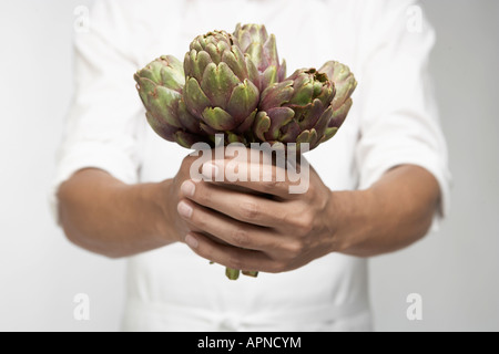 Chef holding artichokes (mid section) - Stock Photo