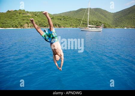 Mid adult man jumping into water, St. John, US Virgin Island, USA - Stock Photo