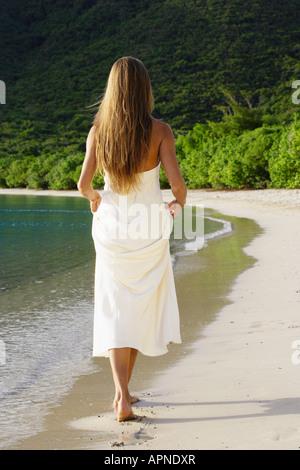 Mid adult woman in wedding dress walking on beach, St John, US Virgin Islands, USA - Stock Photo
