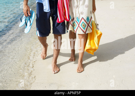 Couple walking on sandy beach (low section)