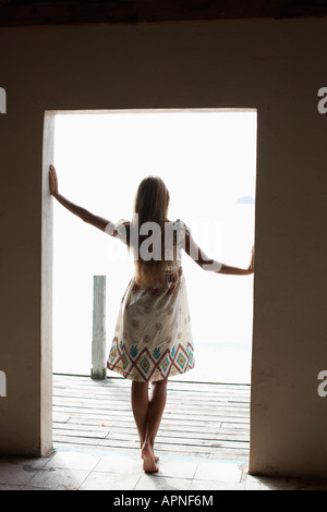 Mid adult woman looking out from doorway - Stock Photo