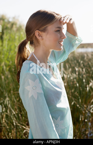 Young woman shielding eyes and looking at view - Stock Photo