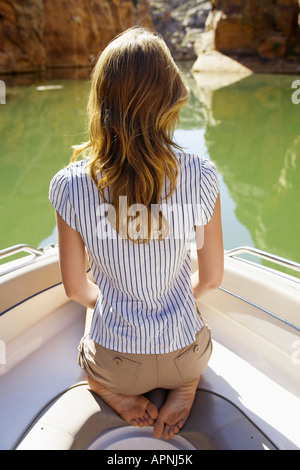 Young woman sitting in boat (rear view) - Stock Photo