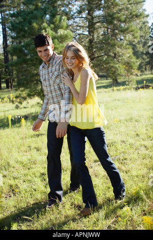 Young couple walking in a field of wildflowers - Stock Photo
