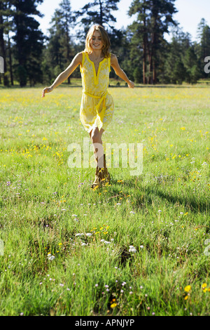 Young woman running in a field of wildflowers - Stock Photo
