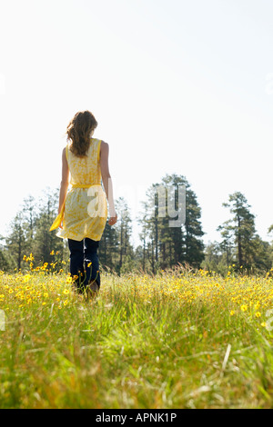 Young woman walking in a field of wildflowers (rear view) - Stock Photo