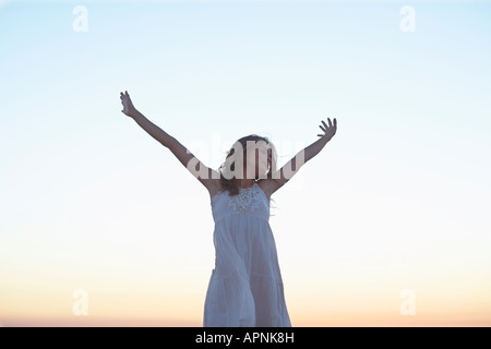 Young woman in white dress raising hands at sunset