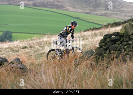 A man riding a mountain bike across moorland. - Stock Photo