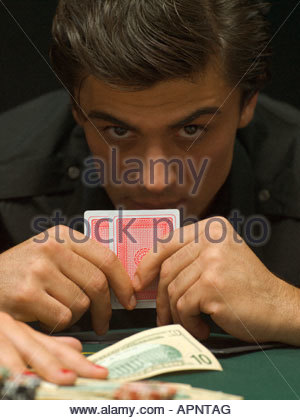 Intense man with playing cards at poker game - Stock Photo