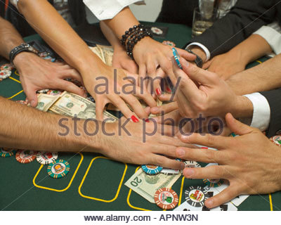 Detail of arms reaching for money at poker game - Stock Photo