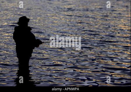 fisherman fly fishing on Stoneyford Reservoir at sunset county antrim northern ireland - Stock Photo