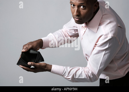 Businessman showing empty wallet - Stock Photo