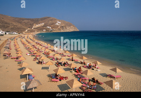 The lines of beach umbrellas shading holiday makers relaxing on the sands of Elia beach on Mykonos - Stock Photo